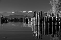 Schweitzer Ski Resort from the Boatworks Marina at Sunnyside Point on Lake Pend Oreille. This shows a dusting of snow on the runs in early November of 2010. Also Fall colors and pilings are reflected. Located near Sandpoint, Idaho. Photo 5 in a series of both color and black and white.