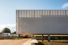 Large concrete columns support a section of the National Confederation of Municipalities office that cantilevers over a shallow pool by Mira Arquitetos