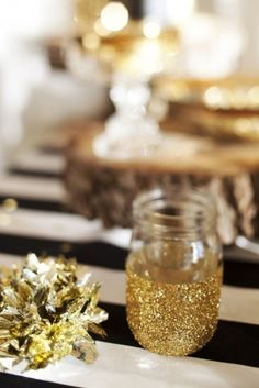 1. Cover half of your mason jar with paper (tape down the edge of the paper to get a smooth line)   2. Spray or paint the other half of the jar with clear glue  3. Dip in glitter   4. Peel of tape and paper  5. After glue dries, brush off excess glitter