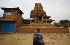 A Nepalese woman examines the damage caused to Bhaktapur Durbar Square in Kathmandu, Nepal after a massive earthquake in there on April 25, 2015.