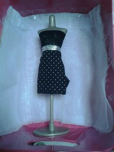 Harumika design #11:this design is a black lace top and a silver belt and a black and white polka dot skirt.