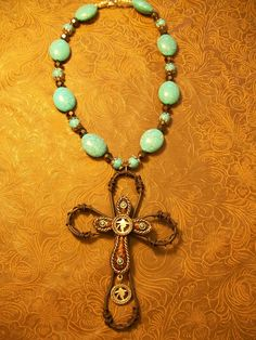 Another beautiful and unique rustic piece! Cross pendant that has the look of rustic wire and leather adorns a turquoise and faceted brown jewel beaded necklace. $30