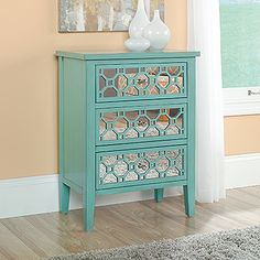 Three drawers feature geometric, mirrored design. Solid wood legs. Seafoam Green finish.