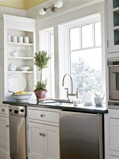 Open window across sink and range.  Side facing cabinets along oven/microwave wall
