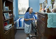 Sister Mary Alice Chineworth adjusts things on the bureau in her room that she's lived in since 1960. She joined the Oblate Sisters of Providence when she was 19.