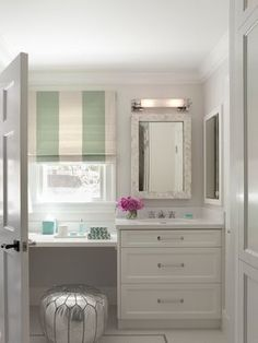 Elegant bathroom with silver Moroccan pouf tucked under a floating dressing table below a sunny window dressed with a white and jade green striped roman shade which accents with dressing table decor.