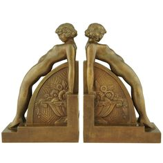 A pair of Art Deco bookends with nudes.  The center has a relief decorated vase with flowers. By François Victor Bazin.