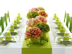 Green place settings with green and pink palette centerpieces.
