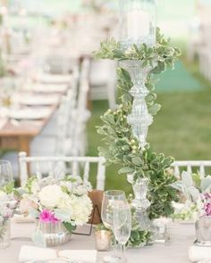 Tall crystal candelabras wrapped in lush garlands create height variation when mixed in among shorter flower arrangements