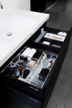 Acrylic organisers in the bathroom vanity help to keep makeup organised and…