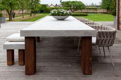 Industriële tuintafel met een tafelblad van beton en de poten van cortenstaal.