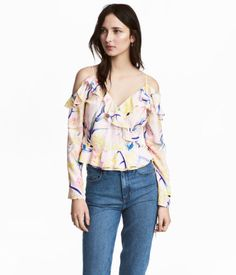 Light pink/floral. Wrap-front, open-shoulder blouse in woven fabric with narrow shoulder straps and long sleeves. Ruffles at front, tie at one side, and