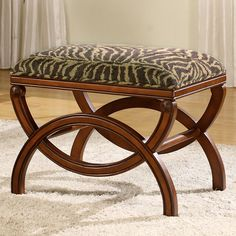This traditional upholstered stool features a beautiful carved wood frame base and animal print upholstered seat.