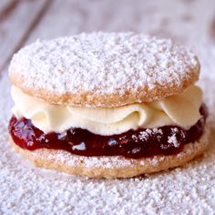 Small round discs of delicate sponge cake with jam and fresh cream in the centre and dusting of icing sugar.