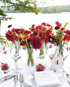 A smattering of slim glass vases at every table puts loose, garden-style arrangements of dahlias, ranunculus, zinnias, nerines, scabiosa, and maiden-hair fern on display at Lauren and Craig's garden fete.