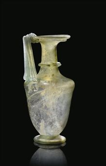 A ROMAN GREEN BLOWN GLASS JUG  3RD-4TH CENTURY A.D., EASTERN MEDITERRANEAN  The amphora-shaped body with carinated shoulder, tall cylindrical neck and conical flared rim, the circular foot folded with tubular edge, a thick trail around base of neck and underside of rim, with broad and ribbed strap handle folded down under the rim and back up over its edge  6¼ in. (16 cm.) high