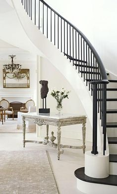 Under the curvy staircase, an antique French table with worn painted wood was updated with a new marble top. A dark banister and steps provide striking contrast.
