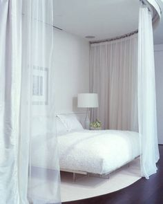"""To make the bed feel sensual and mysterious, designer Benjamin Noriega-Ortiz enclosed it in a layer of transparent fabric. The mattress has a thick feather pillow on top that helps create the illusion of being on """"cloud nine."""" By keeping the bed off the floor, the designer reinforced the idea of floating."""