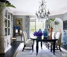 """When Lucky Brand execs Dave DeMattei and Patrick Wade bought their 1920s Beverly Hills mansion, they knew they needed to renovate. """"The house was in good shape, but it was basically a vanilla box,"""" DeMattei says. They gave the dining room personality by pairing gray walls with curtains of a modern print from Barclay Butera Home. (September 2013)"""