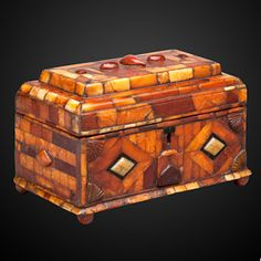 Amber Box  ~  19th century  ~  The surface of this amber box, made for the Ottoman market, is covered with polygonal panels of amber, the front with a design centred around two diamond-shaped lozenges with four fan-motifs in the corners. The interior is lined in silk.  Origin: Probably Polish.