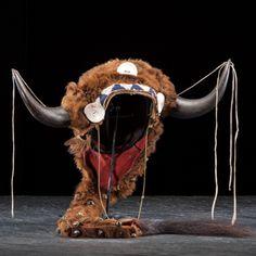 Головной убор, Северные Равнины. Вид один. Кожа и рога бизона, зелёная и красная шерсяная ткань, 20 медных колокольчиков вдоль трейлера, три диска из ракушек, белый и тёмно синий бисер. Общая длина 48 дюймов. Период 1900. Коллекция Денвера, Колорадо. Cowan's.  9/23/2016 – American Indian and Western Art.