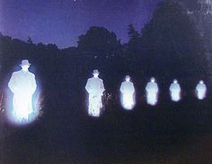 glowing men statues night light sky trees