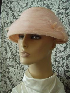 1950's Pink Tulle Beehive hat.  The netting is gathered in layers with two small pink bows.  The hat brim is tapered to a short back.