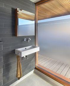 This bathroom features grey tile and frosted glass.