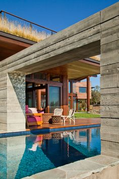 an arch over this modern swimming pool is part of the wall that continues through to - Acristalar Terraza
