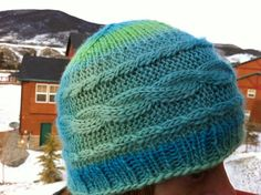 Free knitting pattern -- cabled hat that uses less than one skein of worsted weight yarn.