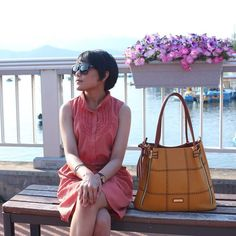 sleeveless chiffon dress in front of 공지천. Short hair and sunglasses.
