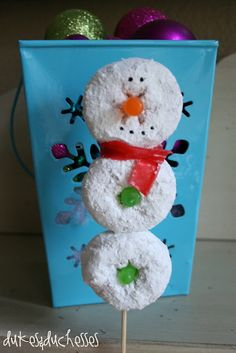 I made the snowmen on a skewer, inspired by the cute snowmen at A Little Tipsy, with a couple of changes.  I used an orange Mike and Ike for the nose and a green Mike and Ike cut in half for the buttons.  A slice of fruit roll-up makes up the scarf, and the eyes and mouth are made from a toothpick dipped in black food coloring and then touched onto the donut.  I wanted to minimize the amount of candy used and simplify the process.  I think they turned out really cute!