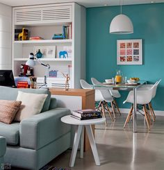 Sala de jantar e estar modernas, com jogos de cores. Destaques: cor parede, cadeiras, mesa de canto, lustre e estante.