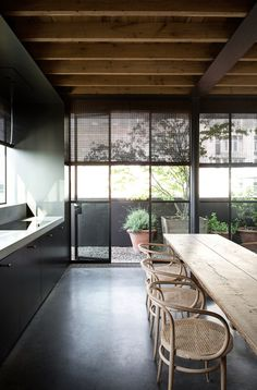 Wood beams, black windows, walls & floors, love the Thonet chairs with rustic harvest table