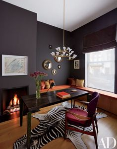 A dramatic light fixture adds a dash of whimsy to this black-painted office inside a New York City townhouse | archdigest.com