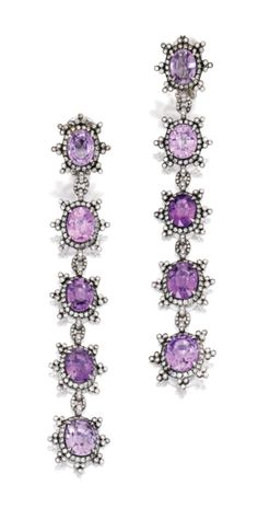 Pair of 18 Karat White Gold, Sapphire and Diamond Earclips. Of columnar design, set with ten oval-shaped purple sapphires weighing 29.00 carats, framed and accented by round diamonds weighing 3.25 carats, signed Fred Leighton.