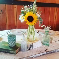 This country wedding with no burlap called for barn wood table runners. Vintage milk bottles held the centerpieces with sunflowers as the main attraction. Turquoise was the accent color, so we used as many turquoise vintage bottles as we could find, alongside some candle holders.