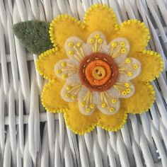 "2 1/2"" yellow felt flower brooch, edged in tiny yellow Toho seed beads. There is a smaller ivory felt flowered atop the yellow which is embellished with yellow stitching and seed beads. The center is two layers of shades of orange felt with a little button center. A perfect pin for"