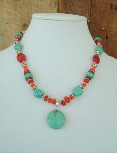 Fabulous Southwest color.....    Gorgeous layers of bright Turquoise and sunny orange Carnelian nuggets, bold red Coral and bronze shell discs. This stunning Southwest style necklace, also has bright Czech glass beads and tribal style silver accents. This beautiful necklace is finished off with a marvelous turquoise circle pendant.    Length – 19 1/2 inches, with a 2 inch extension chain Your purchases will be gift boxed and lovingly wrapped for a gift, or for yourself, to enjoy.    ✽ Thank…