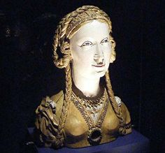 a photo of a medieval reliquary based on the face of an unknown medieval female saint in a display case