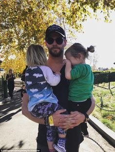 Papa bear! Chris Hemsworth was pictured holding one of his twins in each arm as he posed nonchalantly in a park