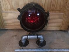 """Antique railroad railway crossing table lamp, the base is made with black iron, brass & galvanized industrial pipe fittings, it has an 8"""" diameter red globe and stands 15"""" high. The light works and has the original DC lights inside, it comes with a DC transformer. It could be set in the middle of your model train tracks and made to turn on when the train passes. Asking $220."""