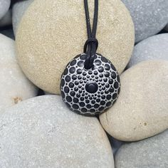 This hand-painted rock mandala necklace is made from natural stone from the beaches of the French Riviera. It is painted metallic silver, with detailing in black, with a slightly lighter shade to finish each dot. The stone has been coated twice with a clear satin varnish. The necklace