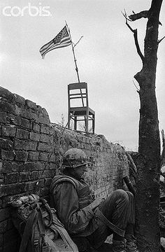 19 Feb 1968, Hue, South Vietnam --- A Marine radioman takes a breather along the wall of the Citadel in Hue.  A makeshift flagpole and a chair support the American flag which flies over the command post of Delta Company. --- Image by © Bettmann/CORBIS