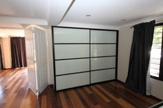 Panel sliding wardrobe doors using white glass panels and black frames. The wardrobe doors look great with timber floors. www.formfunctionnt.com.au