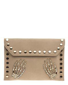 Tuff kuvertväska med skeletthänder och platta stora nitar i guldfärgad metall. En löstagbar axelrem följer med.