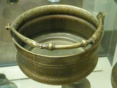 Cast brass bucket, tinned interior. Straight sides and two flarings below the rim and above the base. A cast hoop handle with dragon heads is attached through two lugs projecting from the rim with case and decorated washers forming the terminals of which only one now remains. The interior is tinned.