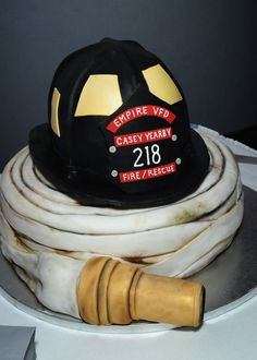 A special cake to honor a local firefighter. Helmet made of rice krispies and covered with fondant. Hose is chocolate cake covered in fondant. Unique Cakes, Creative Cakes, Firefighter Grooms Cake, Firefighter Cupcakes, Firefighter Family, Firefighter Decor, Grooms Cake Tables, Groom Cake, Fireman Wedding