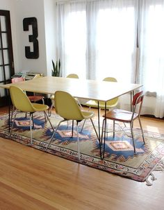 so in love with this dining space ~ the white walls & wod floors provide such a fresh & airy feeling to the space while the bright colors in the chairs add visual interest & warmth and the rug grounds the bright punches of color to keep it from feeling to stark & modern and adds the perfect amount of cozy ~ photo from the home of Rachel, of Smile & Wave blog