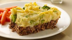 Fluffy mashed potatoes with broccoli tastefully top homemade meat loaf.